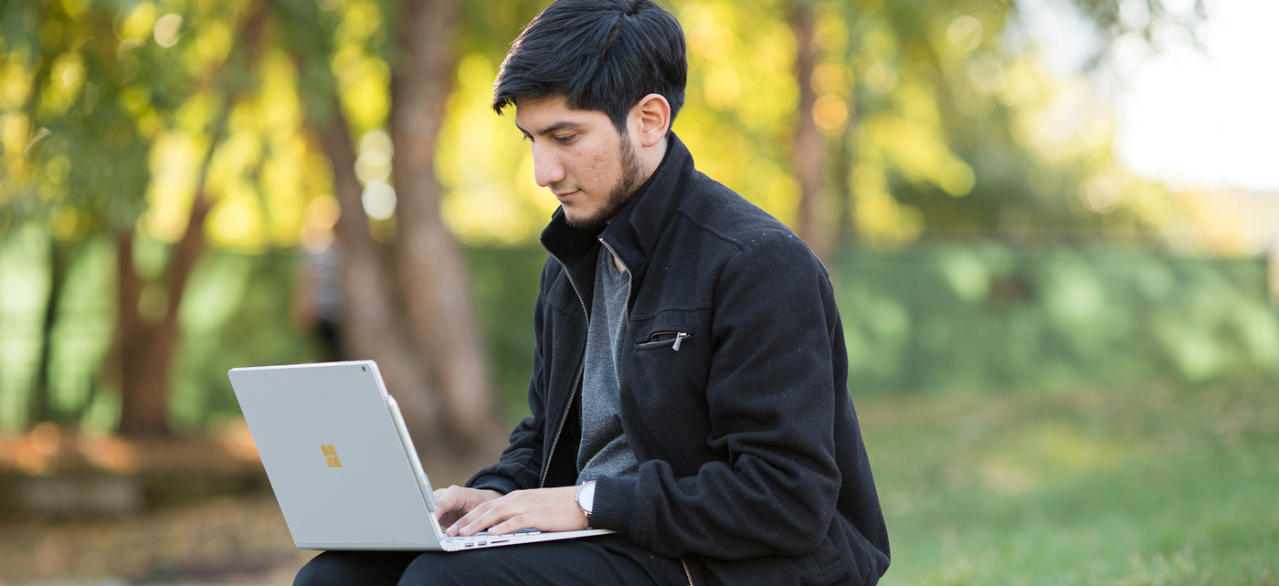 Student uses laptop outside